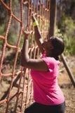 Καθορισμένη γυναίκα που αναρριχείται σε ένα δίχτυ κατά τη διάρκεια της σειράς μαθημάτων εμποδίων Στοκ Φωτογραφίες