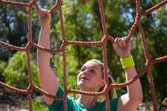 Καθορισμένη γυναίκα που αναρριχείται σε ένα δίχτυ κατά τη διάρκεια της κατάρτισης σειράς μαθημάτων εμποδίων Στοκ Εικόνες