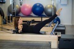 Καθορισμένη γυναίκα που ασκεί τεντώνοντας την άσκηση στο μεταρρυθμιστή Στοκ Φωτογραφία