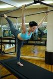 Καθορισμένη γυναίκα που εκτελεί την τεντώνοντας άσκηση στα pilates cadillac Στοκ εικόνες με δικαίωμα ελεύθερης χρήσης