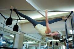 Καθορισμένη γυναίκα που εκτελεί την τεντώνοντας άσκηση στα pilates cadillac Στοκ Εικόνες