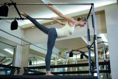 Καθορισμένη γυναίκα που εκτελεί την τεντώνοντας άσκηση στα pilates cadillac Στοκ Εικόνα