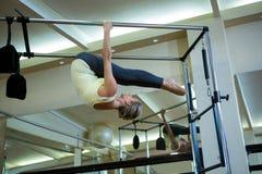 Καθορισμένη γυναίκα που εκτελεί την τεντώνοντας άσκηση στα pilates cadillac Στοκ φωτογραφίες με δικαίωμα ελεύθερης χρήσης