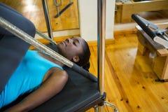 Καθορισμένη γυναίκα που εκτελεί την τεντώνοντας άσκηση στο μεταρρυθμιστή Στοκ εικόνα με δικαίωμα ελεύθερης χρήσης