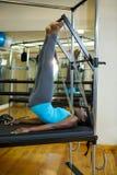 Καθορισμένη γυναίκα που εκτελεί την τεντώνοντας άσκηση στο μεταρρυθμιστή Στοκ Εικόνες