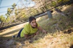 Καθορισμένη γυναίκα που σέρνεται κάτω από το δίχτυ κατά τη διάρκεια της σειράς μαθημάτων εμποδίων Στοκ εικόνες με δικαίωμα ελεύθερης χρήσης