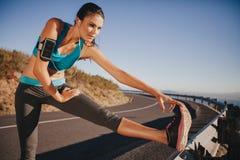 Καθορισμένη νέα γυναίκα που θερμαίνει πριν από ένα τρέξιμο Στοκ εικόνα με δικαίωμα ελεύθερης χρήσης