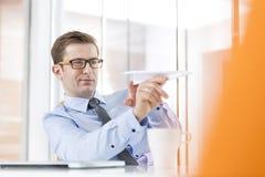 Καθορισμένος επιχειρηματίας που στοχεύει το αεροπλάνο εγγράφου στην αρχή στοκ εικόνα