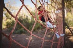 Καθορισμένο αγόρι που αναρριχείται σε ένα δίχτυ κατά τη διάρκεια της σειράς μαθημάτων εμποδίων Στοκ εικόνα με δικαίωμα ελεύθερης χρήσης