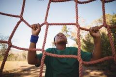 Καθορισμένο αγόρι που αναρριχείται σε ένα δίχτυ κατά τη διάρκεια της σειράς μαθημάτων εμποδίων Στοκ εικόνες με δικαίωμα ελεύθερης χρήσης