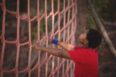 Καθορισμένο αγόρι που αναρριχείται σε ένα δίχτυ κατά τη διάρκεια της σειράς μαθημάτων εμποδίων Στοκ Φωτογραφία