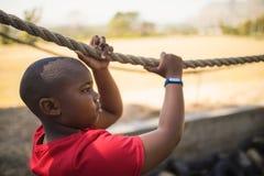 Καθορισμένο αγόρι που διασχίζει το σχοινί κατά τη διάρκεια της σειράς μαθημάτων εμποδίων Στοκ Εικόνα