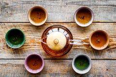 καθορισμένο τσάι τελετή&sigma Teapot γυαλιού και κεραμικά φλυτζάνια στην αγροτική ξύλινη τοπ άποψη υποβάθρου Στοκ Φωτογραφίες