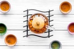 καθορισμένο τσάι τελετή&sigma Teapot γυαλιού και κεραμικά φλυτζάνια στην άσπρη ξύλινη τοπ άποψη υποβάθρου Στοκ Εικόνες