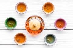 καθορισμένο τσάι τελετή&sigma Teapot γυαλιού και κεραμικά φλυτζάνια στην άσπρη ξύλινη τοπ άποψη υποβάθρου Στοκ εικόνες με δικαίωμα ελεύθερης χρήσης