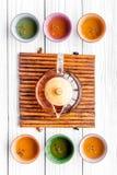 καθορισμένο τσάι τελετή&sigma Teapot γυαλιού και κεραμικά φλυτζάνια στην άσπρη ξύλινη τοπ άποψη υποβάθρου Στοκ φωτογραφία με δικαίωμα ελεύθερης χρήσης