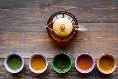 καθορισμένο τσάι τελετή&sigma Teapot γυαλιού και κεραμικά φλυτζάνια στη σκοτεινή ξύλινη τοπ άποψη υποβάθρου copyspace Στοκ εικόνα με δικαίωμα ελεύθερης χρήσης