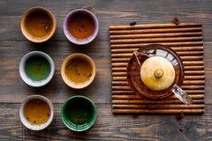 καθορισμένο τσάι τελετή&sigma Teapot γυαλιού και κεραμικά φλυτζάνια στη σκοτεινή ξύλινη τοπ άποψη υποβάθρου Στοκ φωτογραφίες με δικαίωμα ελεύθερης χρήσης