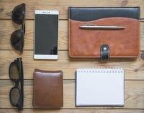 Καθορισμένο υπόβαθρο ατόμων ` s: smartphone, γυαλιά ηλίου, μάνδρα, πορτοφόλι και σημειωματάριο Στοκ Φωτογραφίες