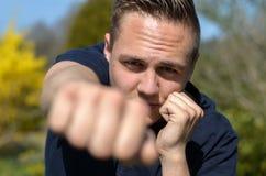 Καθορισμένο punching νεαρών άνδρων στη κάμερα στοκ φωτογραφία