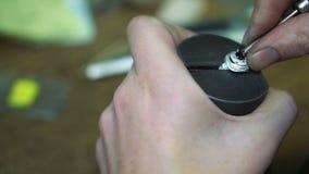 Καθορισμός ενός κόκκινου πολύτιμου λίθου στο κέντρο ενός ασημένιου δαχτυλιδιού που χρησιμοποιεί το εργαλείο φιλμ μικρού μήκους