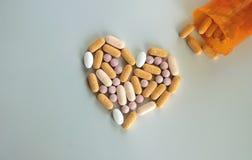 Καθοδηγητικά φάρμακα και χάπια σε μια μορφή καρδιών Στοκ Εικόνες