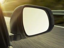Καθρέφτες άποψης στα αυτοκίνητα στον ήλιο ρύθμισης, θολωμένο τοπίο στοκ εικόνες
