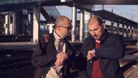 Καθυστέρηση τραίνων Δύο άτομα στο ηλιοβασίλεμα στην πλατφόρμα του σιδηροδρομικού σταθμού που εξετάζει το ρολόι και που περιμένει  απόθεμα βίντεο