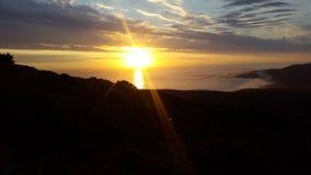 Καθώς ο ήλιος πηγαίνει κάτω και οι ελαφριές ακτίνες εμπρός πέρα από τον ωκεανό Στοκ Εικόνα
