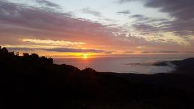 Καθώς ο ήλιος πηγαίνει κάτω και οι ελαφριές ακτίνες εμπρός πέρα από τον ωκεανό Στοκ Φωτογραφίες