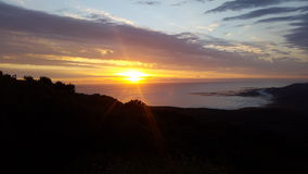 Καθώς ο ήλιος πηγαίνει κάτω και οι ελαφριές ακτίνες εμπρός πέρα από τον ωκεανό Στοκ φωτογραφίες με δικαίωμα ελεύθερης χρήσης