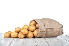 Καινούριες πατάτες σε μια τσάντα σε έναν άσπρο ξύλινο πίνακα απομονωμένος σε ένα W Στοκ Εικόνες