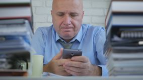 Και απογοητευμένος επιχειρηματίας που διαβάζει το κινητό τηλεφωνικό μήνυμα στο δωμάτιο γραφείων στοκ φωτογραφίες με δικαίωμα ελεύθερης χρήσης