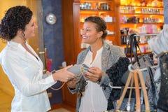 Και ευτυχής πελάτης και πωλητής στην αρωματοποιία Στοκ Εικόνες