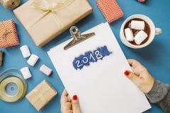 2018 και καυτό κακάο με marshmallows, δώρα, έγγραφο συσκευασίας, ψαλίδι σε έναν μπλε πίνακα Τοπ όψη Στοκ Εικόνες