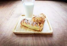 Και οι δύο από την πίτα στο ξύλινο πιάτο με το γάλα Στοκ Εικόνα