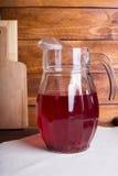 Και υγιής κόκκινος χυμός χυμού φρούτων σε μια κανάτα γυαλιού στο W Στοκ Φωτογραφία