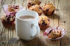 Κακάο φλυτζανιών με το γάλα και σπιτικά μαύρα muffins μούρων στοκ φωτογραφίες