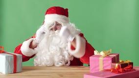 Κακός Άγιος Βασίλης μιλά στο τηλέφωνο, κτυπά την πυγμή του στον πίνακα, κάθεται στον πίνακα με τα δώρα, πράσινο chromakey φιλμ μικρού μήκους