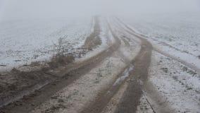 Κακός αγροτικός δρόμος καλλιεργήσιμου εδάφους στο υγρές χειμερινό χιόνι και την υδρονέφωση πρωινού απόθεμα βίντεο