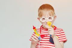 Κακός παίζοντας γιατρός αγοριών Σύριγγα παιχνιδιών, γυαλιά και phonend Στοκ Φωτογραφία