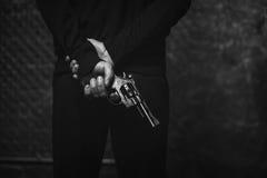Κακός προκλητικός εγκληματίας που κρύβει ένα όπλο Στοκ Εικόνες