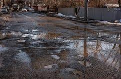 Κακός δρόμος με τις τρύπες και τις λακκούβες Στοκ Εικόνες
