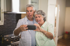 Κακό ανώτερο ζεύγος που παίρνει selfie στην κουζίνα στοκ φωτογραφίες