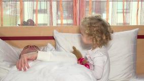 Κακό χαριτωμένο άλμα κοριτσιών στον μπαμπά πατέρων ύπνου της στο κρεβάτι απόθεμα βίντεο