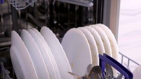 Καλάθια πλυντηρίων πιάτων με τα βρώμικα άσπρα πιάτα και μαχαιροπήρουνα στην κουζίνα φιλμ μικρού μήκους