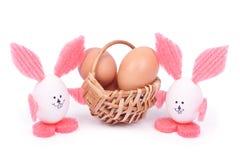Καλάθι με αυγά Πάσχας και δύο κουνέλια στοκ εικόνες