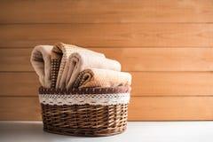 Καλάθι με τις πετσέτες λουτρών στο ξύλινο υπόβαθρο στοκ εικόνες
