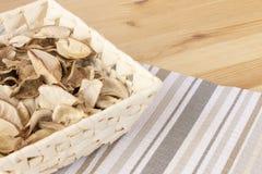 Καλάθι με τις πικάντικες ξηρές εγκαταστάσεις σε ένα ελαφρύ ξύλινο υπόβαθρο, που καλύπτεται με το ριγωτό ύφασμα στοκ φωτογραφίες