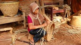 Καλάθι μπαμπού craftswoman κάνοντας την εργασία του στοκ φωτογραφία